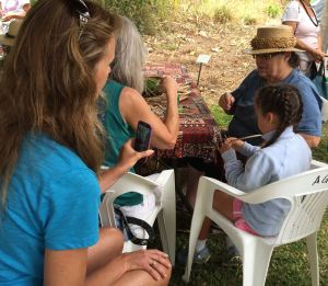 Parents captured their child's lauhala lesson by an elder of the community.
