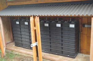 Six Aquion S20+ saltwater batteries sit behind the house in their own shelter, storing electricity each day.